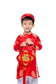 Wietnamski chłopiec przytula faszerowanego karpia. portret przystojny azjatyckiego chłopca na tradycyjny strój festiwalowy. ładny mały wietnamski chłopiec w czerwonej sukience ao dai uśmiechający się.