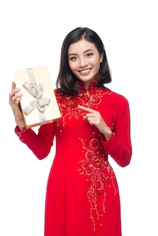 Wietnamski młoda kobieta w sukni ao dai trzyma pudełko.