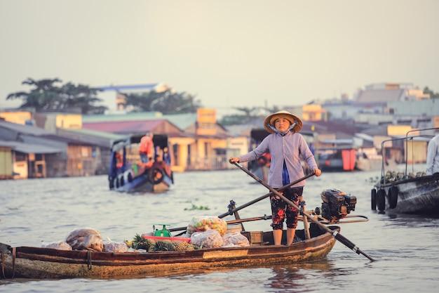 Wietnamski sprzedawca wiosłuje na swojej łodzi na pływającym rynku nga nam w mekong delta wietnam.