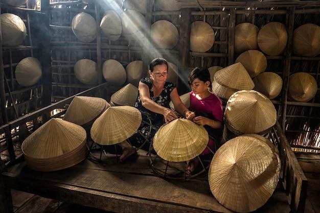 Wietnamski staruszek rzemieślnik uczy wnuka robiącego tradycyjny wietnamski kapelusz