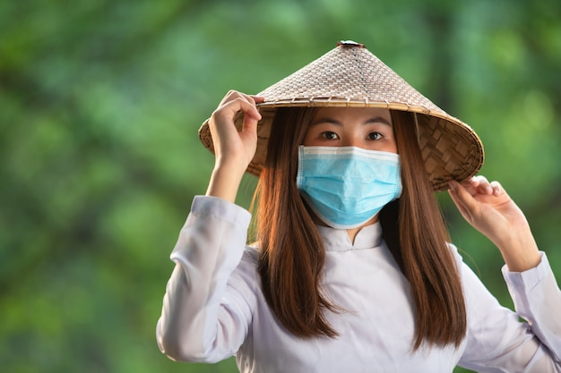 Wietnamskie kobiety noszą maski, ao dai jest znanym tradycyjnym strojem maski, koncepcja zapobiega rozprzestrzenianiu się covid-19 coronavirus koncepcja