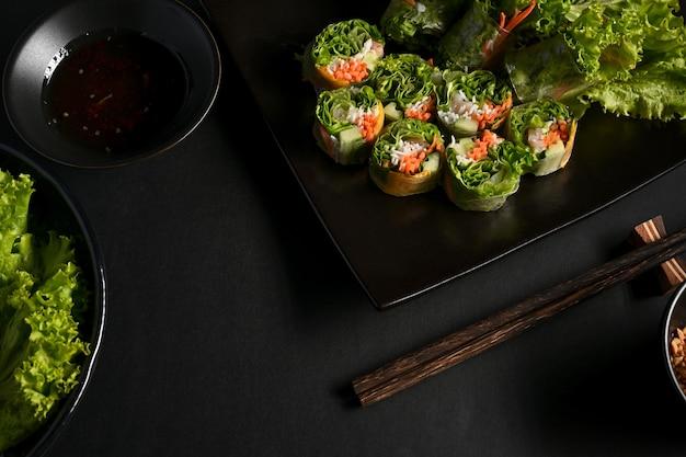 Wietnamskie sajgonki z sosem do maczania i warzywami na stole w jadalni