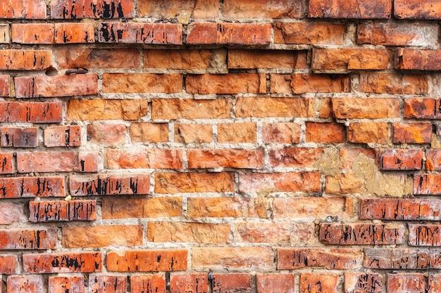Wietrzejący plamiący stary pomarańczowy ściana z cegieł, tekstury grunge tło