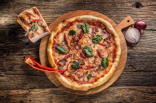 Wiew włoska pizza z cebulą chili bekon i bazylią na drewnianym talerzu i okrągłej desce.
