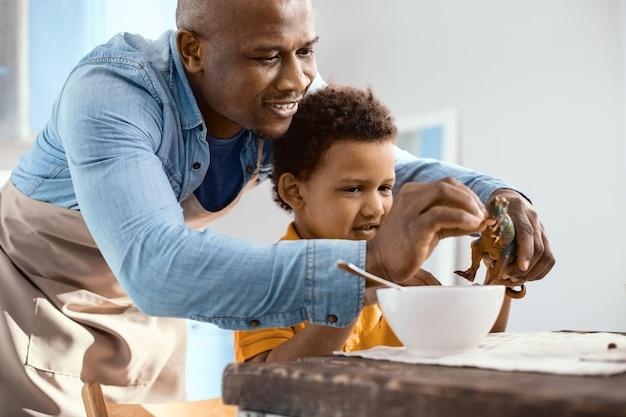 Więź ojciec-syn. uroczy młody ojciec karmiący zbożem zabawkowego dinozaura synów, podczas gdy chłopiec je śniadanie w kuchni