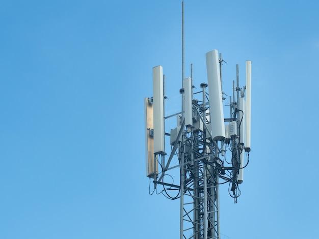 Wieża 5g komunikacji komórkowej lub wieża telekomunikacyjna na błękitnym niebie.