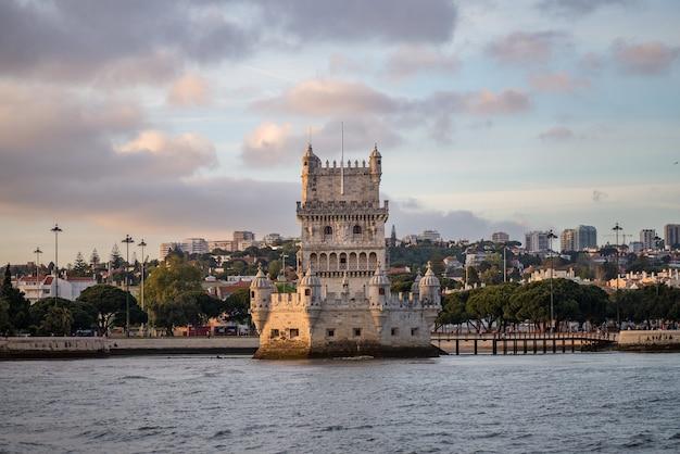 Wieża belem otoczona morzem i budynkami pod zachmurzonym niebem w portugalii