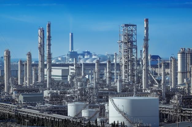 Wieża destylacji gazu i komin stosu ropy naftowej zakładu przemysłowego na tle niebieskiego nieba, w dół rzeki od kopalni ropy naftowej