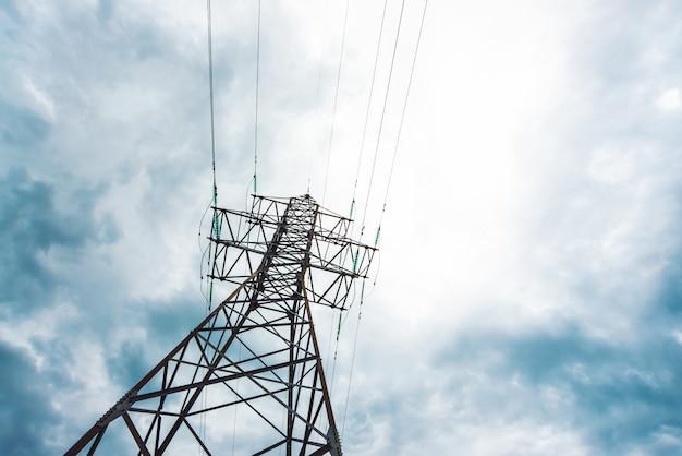 Wieża dystrybucji energii elektrycznej z miejsca kopiowania. wysokie napięcie linie energetyczne pod chmurnym niebem. minimalistyczny widok z dołu na słupy z drutami przy pochmurnej pogodzie. atmosferyczne tło elektryczne.