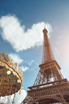Wieża eiffla i karuzela pod chmurą w kształcie serca