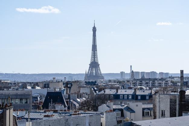 Wieża eiffla otoczona budynkami w słońcu w paryżu we francji