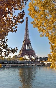 Wieża eiffla w paryżu między żółtymi liśćmi jesienią widok z sekwany