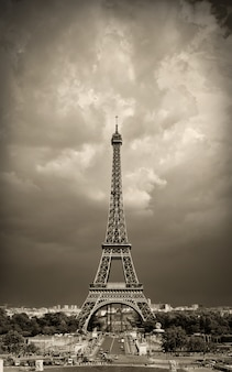 Wieża eiffla w paryżu, w odcieniach sepii na tle dramatycznego nieba.