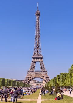 Wieża eiffla w słoneczny, pogodny dzień pole marsa wypełnione ludźmi na pierwszym planie paryż francja