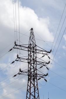 Wieża elektryczna wysokiego napięcia. linie energetyczne i słupy energetyczne w słoneczny dzień z okrągłymi chmurami na niebieskim niebie. wsporniki linii przesyłowych wysokiego napięcia. posiadają złożoną konstrukcję stalową.