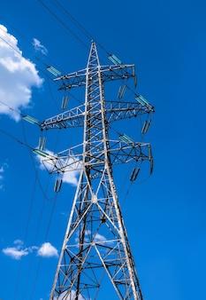 Wieża energetyczna z przewodami elektrycznymi przesyłającymi energię elektryczną na tle błękitnego nieba