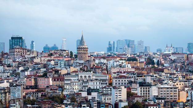 Wieża galata z poziomami budynków mieszkalnych przed nią i nowoczesnymi budynkami przy pochmurnej pogodzie stambuł, turcja