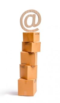 Wieża kartonowych pudeł i symbol e-mail na górze.