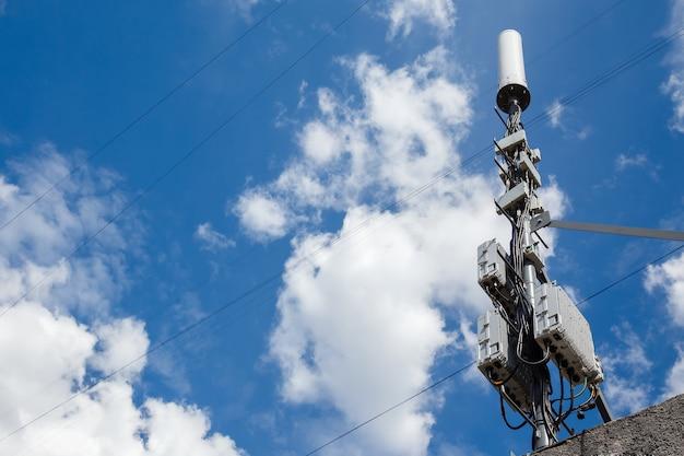 Wieża komórkowa na tle zachmurzone niebo niebieskie