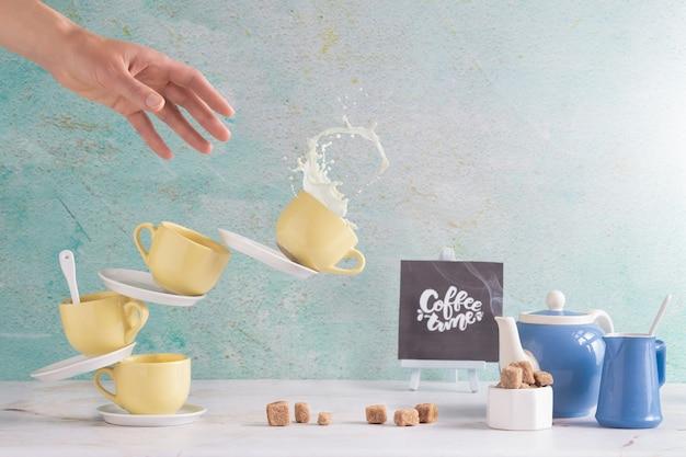 Wieża kubków spada, gdy jedna ręka próbuje je złapać. zestaw do kawy time.selective focus