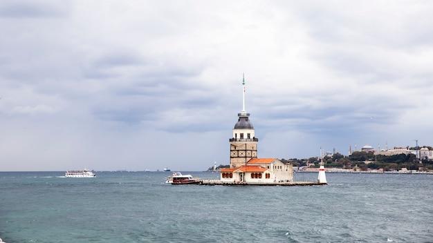 Wieża leandera położona pośrodku cieśniny bosfor, pochmurna pogoda, poruszający się statek i miasto w oddali stambuł, turcja