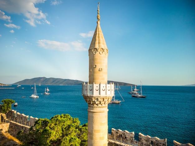 Wieża meczetu kale camisi bodrum z łodziami na morzu i górami na tle meczet umieszczony