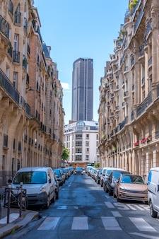 Wieża montparnasse na końcu wąskiej paryskiej ulicy z samochodami