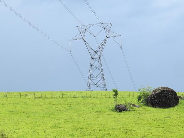 Wieża przesyłu energii zainstalowana w środku zielonego pola na terenach wiejskich