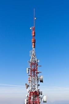 Wieża radiokomunikacyjna z naczyniami na tle głębokiego błękitu nieba
