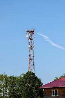 Wieża radiowa tv w mieście, zielone nowoczesne miasto. transmisja sygnałów do różnych części kraju. wieża radiowa tv w mieście, zielone nowoczesne miasto. przenoszenie