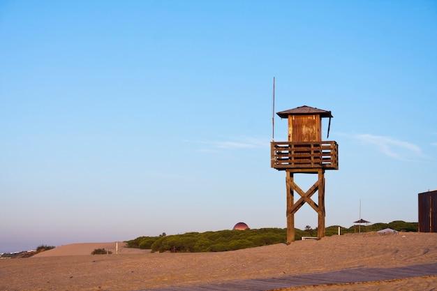 Wieża ratownika na piasku i niebieskim niebie