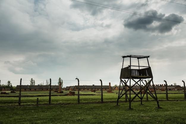 Wieża strażnicza i ogrodzenie z drutu kolczastego, niemiecki obóz koncentracyjny