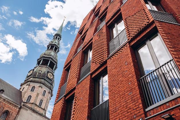 Wieża świętego piotra szeroki kąt. słoneczna pogoda z niebieskim niebem. kościół świętego piotra w historycznym centrum rygi. łotwa