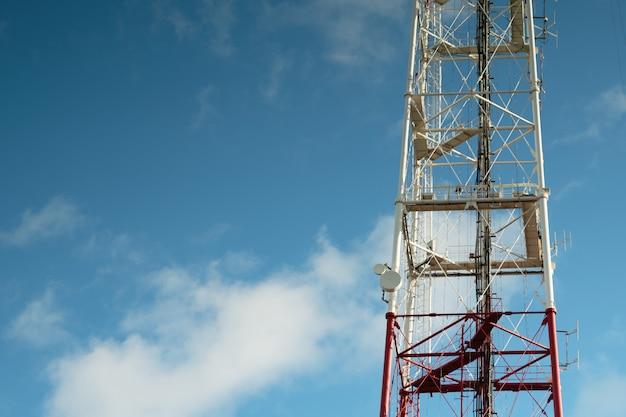 Wieża telekomunikacyjna na tle błękitnego nieba, antena komórkowa, nadajnik. wieża telewizyjna