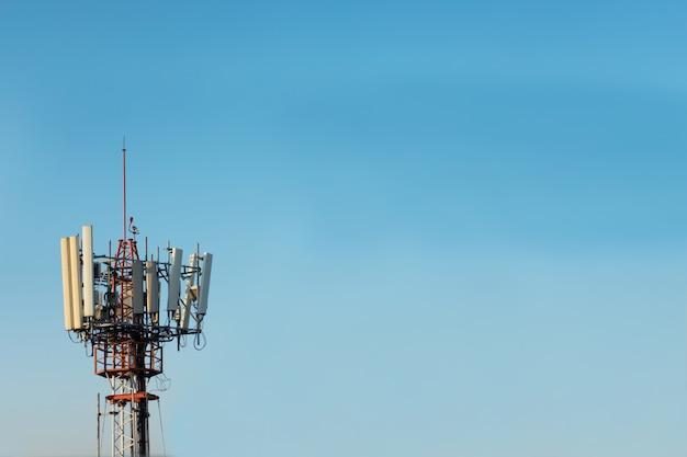 Wieża telekomunikacyjna na tle błękitnego nieba. koncepcja komunikacji bezprzewodowej