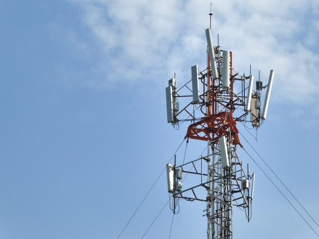 Wieża telekomunikacyjna przeciw błękitne niebo z chmurami.
