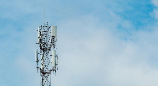 Wieża telekomunikacyjna z błękitne niebo i białe chmury w tle antena na niebieskim niebie biegun radiowy i satelitarny komunikacja