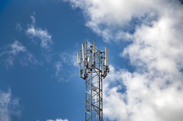 Wieża telekomunikacyjna z nadajnikami 4g, 5g. komórkowa stacja bazowa z antenami nadawczymi na wieży telekomunikacyjnej na tle błękitnego nieba.