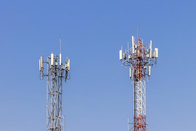Wieża telekomunikacyjna z niebieskim niebem i białymi chmurami w tle, technologia komunikacji słupa satelitarnego.