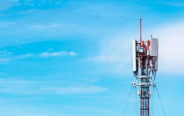 Wieża telekomunikacyjna z niebieskim tle nieba i białych chmur. antena na niebieskim niebie. słup radiowy i satelitarny. technologia komunikacyjna. przemysł telekomunikacyjny. sieć komórkowa lub telekomunikacyjna 4g.