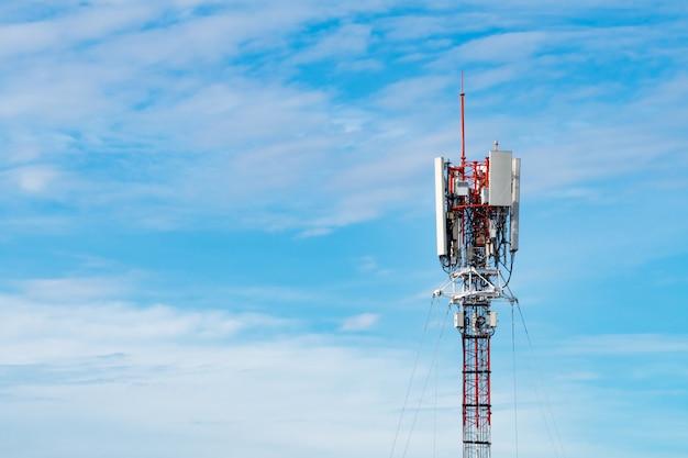Wieża telekomunikacyjna z niebieskim tle nieba i białych chmur. antena na niebieskim niebie.