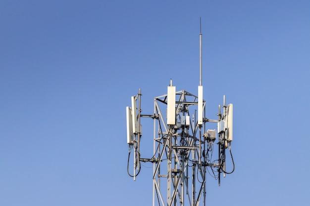 Wieża telekomunikacyjna z niebieskim tle nieba i białych chmur, technologia komunikacji słupa satelitarnego.