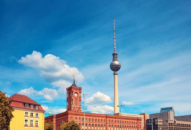 Wieża telewizyjna dalej i czerwony ratusz na alexanderplatz w berlinie w słoneczny dzień