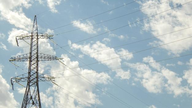 Wieża wysokiego napięcia na tle błękitnego nieba z chmurami