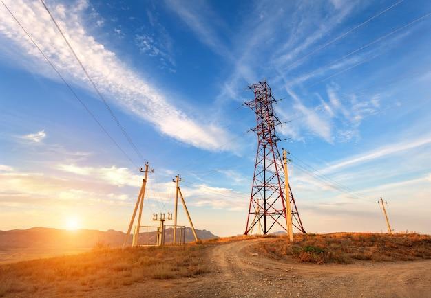 Wieża wysokiego napięcia w górach o zachodzie słońca. system pylonu elektrycznego