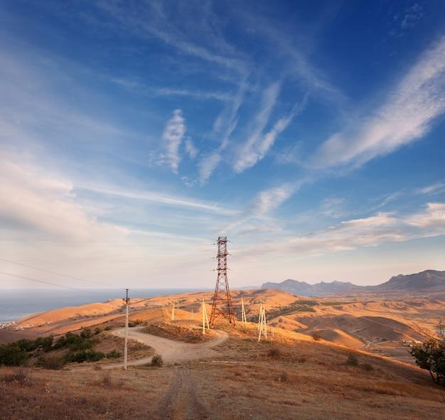 Wieża wysokiego napięcia w górach o zachodzie słońca