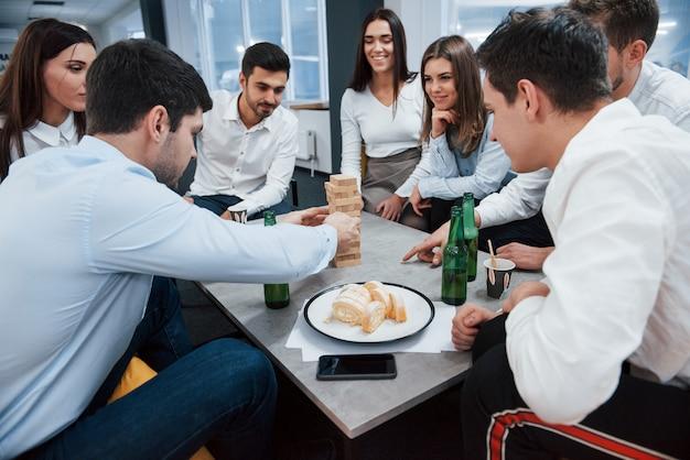 Wieża z cegieł drewnianych. świętowanie udanej transakcji. młodzi urzędnicy siedzący przy stole z alkoholem