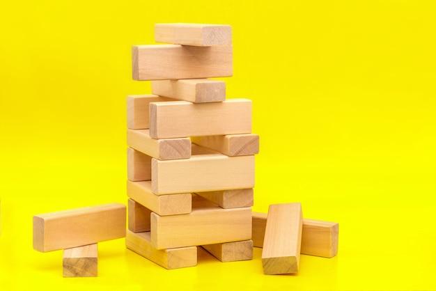 Wieża z drewnianych klocków na żółtym tle z kopią miejsca. koncepcja budowania biznesu lub budowania zespołu.