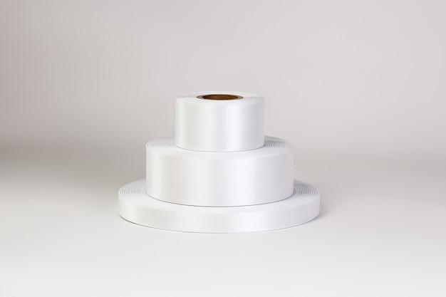 Wieża z trzech zwojów białych satynowych wstążek o różnych rozmiarach do etykiet lub brandingu na białym tle