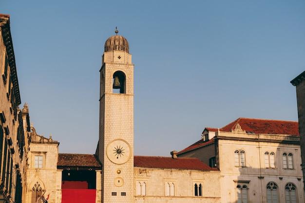 Wieża zegarowa w dubrowniku o zachodzie słońca z murów miejskich